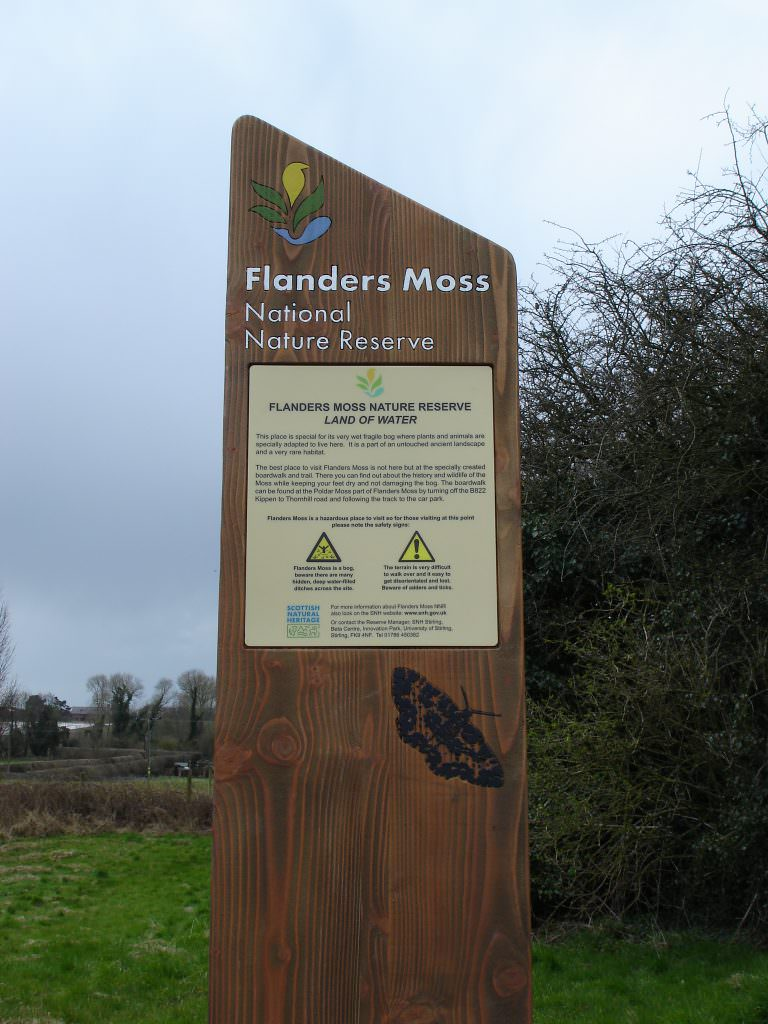 A secondary reserve entrance sign consisting of a single sandblasted Cedar plank and a full colour printed plaque set into the wood.