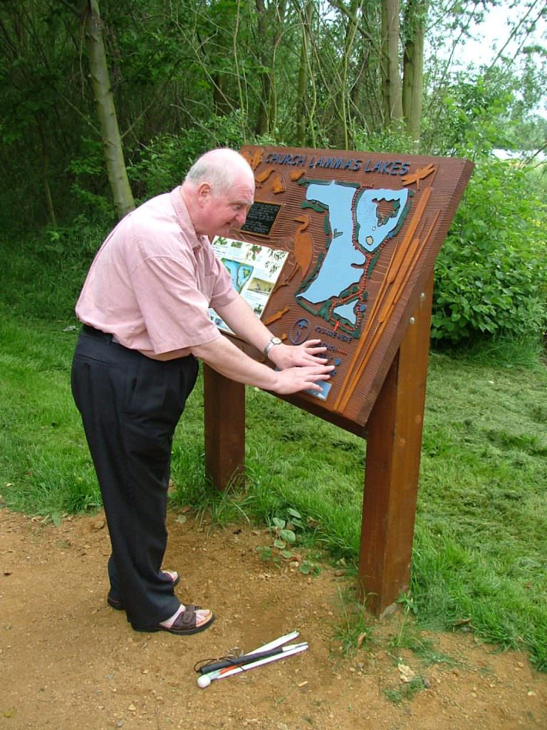 A man reading a tactile map panel with his fingers.  The panel includes tactile text & map, a Braille plaque and a full colour printed section