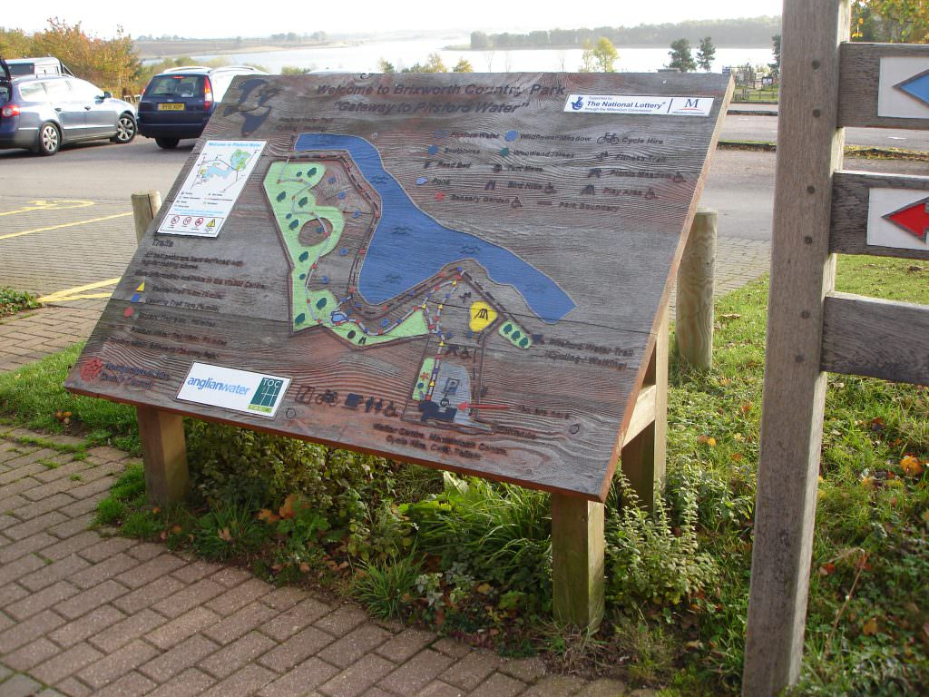 A large tactile map on a lectern frame, set in a country park.  The design shows walks around the lake and introduces local natural history