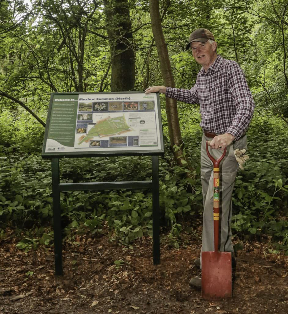 A natural history themed interpretation panel or board complete with a powder coated aluminium lectern frame. It has just been installed by a volunteer with a spade