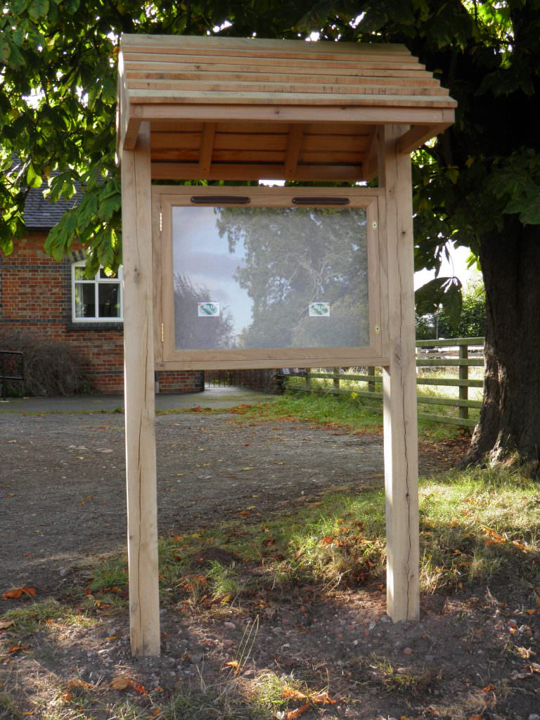 An Oak lockable notice board and posts with a pitched roof shelter for protection from the elements. Located by a rural parish hall.