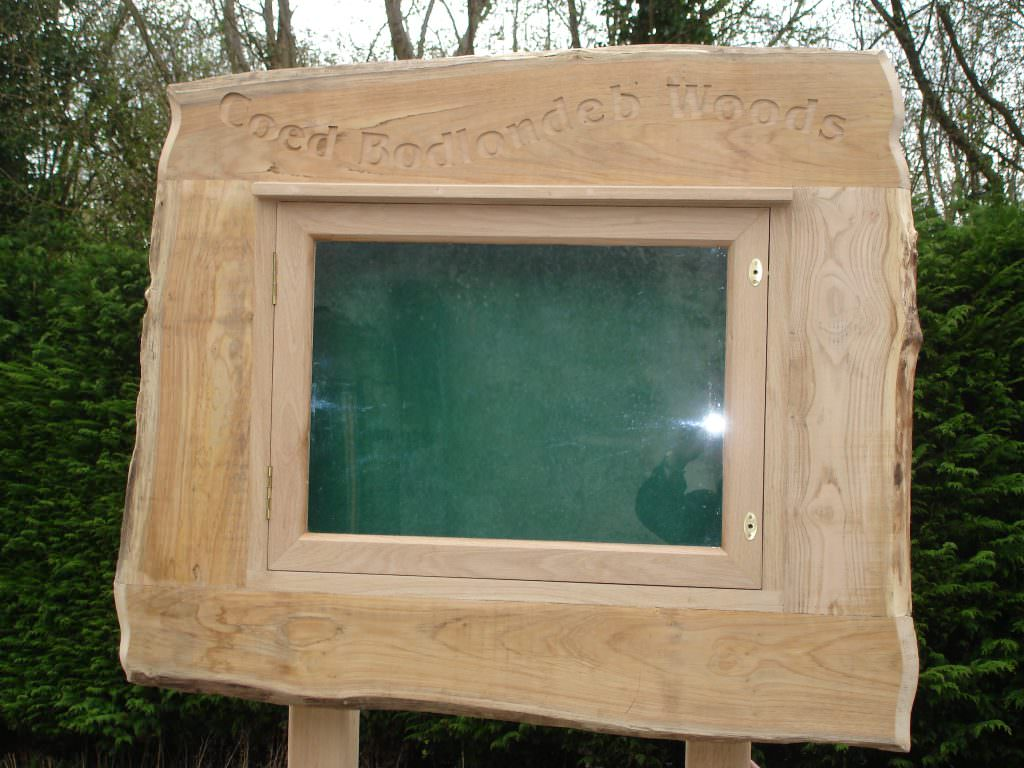 Close up picture of an Oak lockable notice board with shaped and decorated sides. Mounted on oak posts