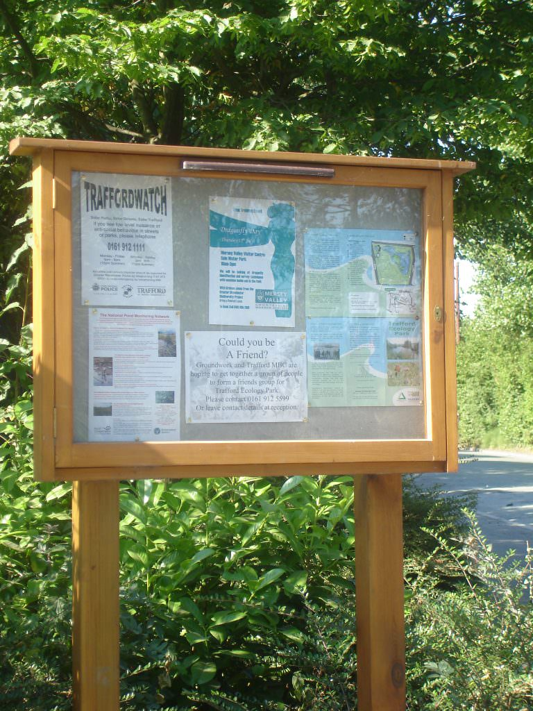 A lockable oak notice board at A1 size to display 8 sheets of A4 paper. Seen with a pinboard backer and oak posts. Ina rural setting.
