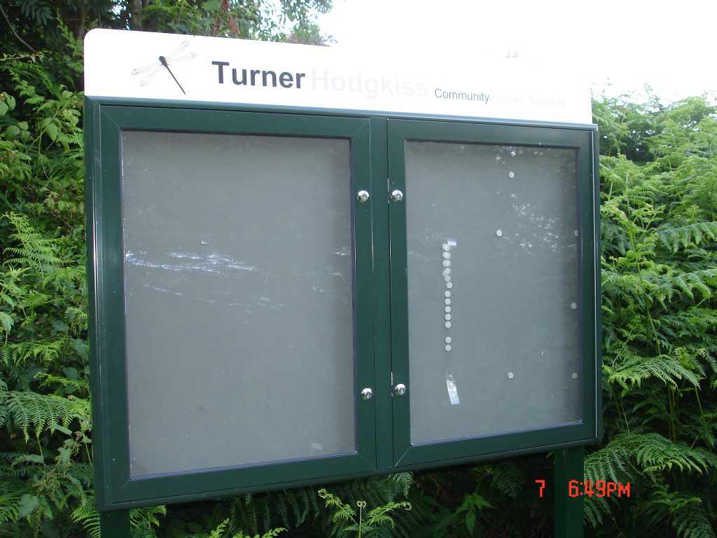 A twin door aluminium notice board, each door lockable. It has a printed header panel and powder coated posts. Located in a nature reserve.
